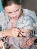 Mutter, die ihr Kind speist Lizenzfreie Stockfotos