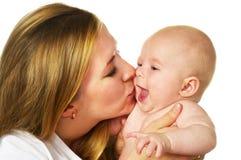 Mutter, die ihr lachendes Baby küßt Stockfoto
