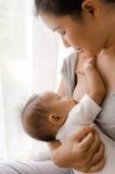 Mutter, die ihr neugeborenes Baby neben Fenster stillt Stockbilder