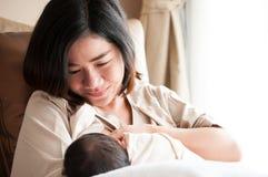 Mutter, die ihr neugeborenes Baby neben Fenster stillt Milch von Mutter ` s Brust ist ein Naturheilverfahren zum Baby Muttertag c Lizenzfreie Stockfotos
