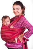 Mutter, die ihr Schätzchen in einem Riemen trägt Lizenzfreies Stockfoto