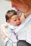 Mutter, die ihr Schätzchen in einem Riemen trägt lizenzfreie stockfotos
