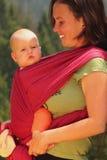 Mutter, die ihr Schätzchen in einem Riemen trägt lizenzfreie stockbilder