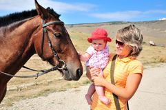 Mutter, die ihr Schätzchen mit Pferd gewöhnt Lizenzfreie Stockfotos