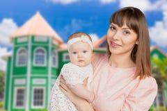 Mutter, die ihre Babytochter hält Lizenzfreie Stockbilder