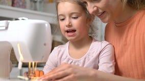 Mutter, die ihre kleine Tochter unterrichtet, unter Verwendung einer Nähmaschine in der Kindertagesstätte zu Hause zu nähen stock footage
