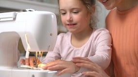 Mutter, die ihre kleine Tochter unterrichtet, unter Verwendung einer Nähmaschine in der Kindertagesstätte zu Hause zu nähen stock video