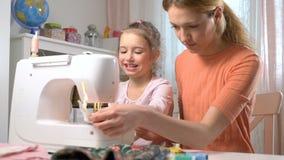 Mutter, die ihre kleine Tochter unterrichtet, unter Verwendung einer Nähmaschine in der Kindertagesstätte zu Hause zu nähen stock video footage