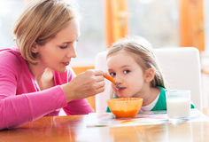 Mutter, die ihre Tochter durch Löffel speist lizenzfreies stockfoto