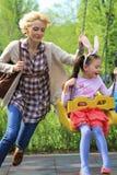 Mutter, die ihre Tochter in einem Karussell spinnt Lizenzfreies Stockfoto