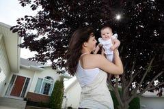 Mutter, die ihre Tochter hält Lizenzfreies Stockfoto