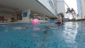 Mutter, die ihre Tochter unterrichtet, im Swimmingpool zu schwimmen stock footage