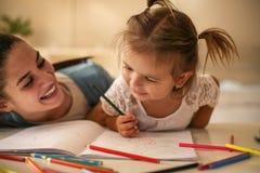 Mutter, die ihre Tochter zum Zeichnen unterrichtet stockfotos