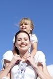 Mutter, die ihre Tochterdoppelpolfahrt gibt stockfotografie