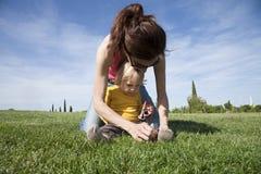 Mutter, die ihre Tochterschuhe bindet Lizenzfreie Stockfotos