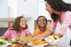 Mutter, die ihren Kindern eine Mahlzeit dient stockfotografie