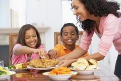 Mutter, die ihren Kindern eine Mahlzeit dient stockbilder