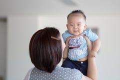 Mutter, die ihren Sohn anhebt Lizenzfreies Stockfoto