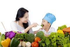 Mutter, die ihren Sohn mit frischem Brokkoli einzieht Stockfotografie
