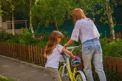 Mutter, die ihrer Tochter beibringt, wie man Fahrrad im Park fährt stockbild