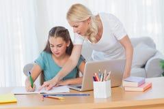 Mutter, die ihrer Tochter hilft, ihre Hausarbeit zu tun Stockfotos