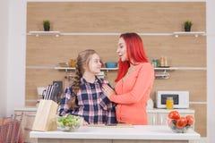 Mutter, die ihrer Tochter Neigung beim Kochen des Brunchs zeigt stockfotografie