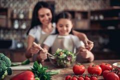 Mutter, die ihrer Tochter wirft den Salat hilft stockbild