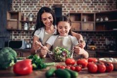Mutter, die ihrer Tochter wirft den Salat hilft lizenzfreies stockbild