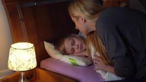 Mutter, die ihrs schlafender Sohn überprüft