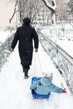 Mutter, die Kind auf Schlitten zieht Lizenzfreie Stockfotografie
