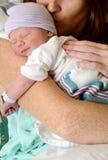 Mutter, die lächelndes neugeborenes Baby küsst Stockbilder