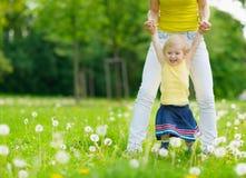 Mutter, die mit Baby auf Löwenzahnfeld spielt Stockbild
