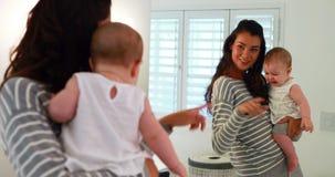 Mutter, die mit ihrem Baby im Badezimmer spielt stock footage