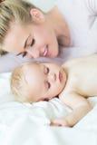 Mutter, die mit ihrem kleinen Baby liegt Stockbilder