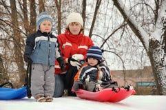 Mutter, die mit ihren Söhnen sledding ist Stockbilder