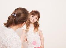 Mutter, die mit ihrer Tochter auf Weiß spielt Stockfoto