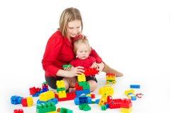 Mutter, die mit Kind über Weiß spielt Stockfotografie
