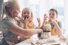 Mutter, die mit Kindern auf der Küche kocht Lizenzfreie Stockbilder
