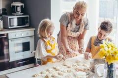 Mutter, die mit Kindern auf der Küche kocht Stockbilder