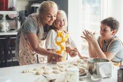 Mutter, die mit Kindern auf der Küche kocht Stockbild