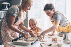 Mutter, die mit Kindern auf der Küche kocht Lizenzfreies Stockbild
