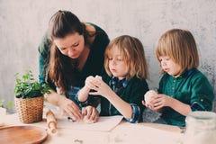 Mutter, die mit Kindern in der Küche kocht Kleinkindgeschwister, die zusammen backen und zu Hause mit Gebäck spielen lizenzfreie stockfotos