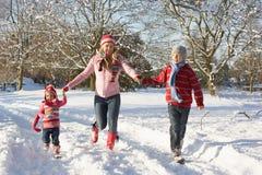 Mutter, die mit Kindern durch Schnee geht Lizenzfreies Stockbild