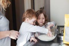 Mutter, die mit Kindern kocht Stockfotos