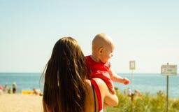 Mutter, die mit Schätzchen auf Strand spielt Stockfotos