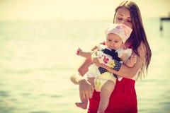 Mutter, die mit Schätzchen auf Strand spielt lizenzfreies stockfoto