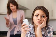 Mutter, die mit Tochter über Gebrauch von Handy argumentiert stockbilder