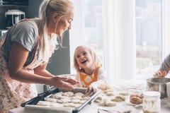 Mutter, die mit Tochter auf der Küche kocht Stockbilder