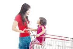 Mutter, die mit Tochter auf Laufkatze lacht Stockbilder