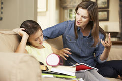 Mutter, die mit Tochter frustriert wird, während, die Hausarbeit tuend, die auf Sofa At Home sitzt lizenzfreie stockfotografie